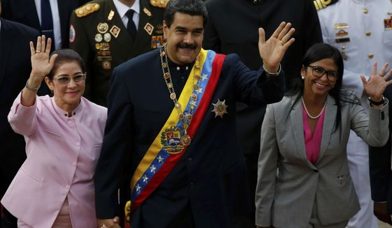Venezuela's President Nicolas Maduro, center, with his wife Cilia Flores, left, and Constitutional Assembly President Delcy Rodriguez wave as they arrive to the National Assembly building for a session with the Constitutional Assembly in Caracas, Venezuela, Thursday, Aug. 10, 2017. (AP Photo/Ariana Cubillos)