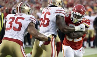Kansas City Chiefs running back Spencer Ware (32) tries to get past San Francisco 49ers linebacker Reuben Foster (56) and safety Eric Reid (35) during the first half of an NFL preseason football game in Kansas City, Mo., Friday, Aug. 11, 2017. (AP Photo/Charlie Riedel)