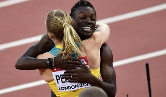 Women's 100 meters hurdles final silver medalist United States' Dawn Harper Nelson embraces gold medalist Australia's Sally Pearson, left, at the World Athletics Championships in London Saturday, Aug. 12, 2017. (AP Photo/Martin Meissner)