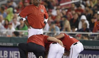 Washington Nationals manager Dusty Baker, top, stands on the field as Bryce Harper, bottom center, receives attention after he was injured during the first inning of a baseball game against the San Francisco Giants, Saturday, Aug. 12, 2017, in Washington. (AP Photo/Nick Wass)