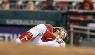 Washington Nationals' Bryce Harper grabs his knee after he was injured running to first during the first inning of the team's baseball game against the San Francisco Giants, Saturday, Aug. 12, 2017, in Washington. (AP Photo/Nick Wass)