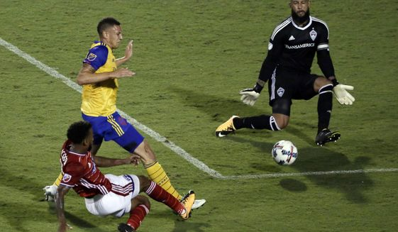 FC Dallas midfielder Kellyn Acosta, bottom left,  shoots as Colorado Rapids's Kortne Ford, top left, and goalie Tim Howard, top right, defend in the second half of an MLS soccer game, Saturday, Aug. 12, 2017, in Frisco, Texas. (AP Photo/Tony Gutierrez)