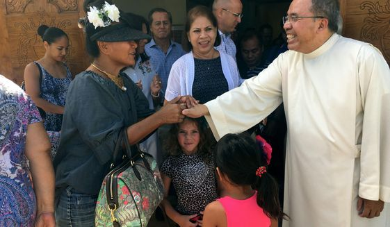 "Pastor Fr. Jose Antonio"" Lito"" P. Abad, right, greets parishioners as they leave Blessed Diego de San Vitores Church following Sunday Mass, Sunday, Aug. 13, 2017, in Tumon, Guam. Across Guam - where nearly everyone is Roman Catholic - priests are praying for peace as residents of the U.S. Pacific island territory face a missile threat from North Korea. (AP Photo/Tassanee Vejpongsa)"