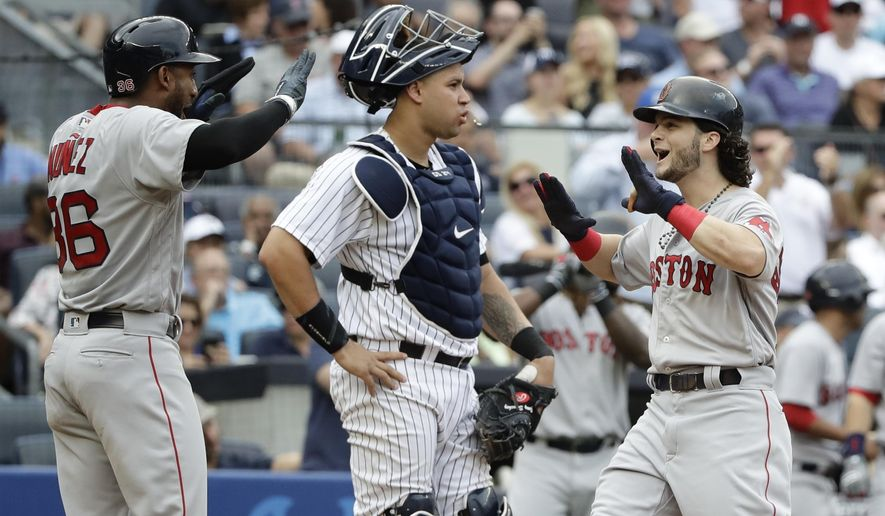Boston Red Sox's Andrew Benintendi, right, celebrates a three-run home run with Eduardo Nunez (36) as New York Yankees catcher Gary Sanchez, center, waits during the fifth inning of a baseball game Saturday, Aug. 12, 2017, in New York. (AP Photo/Frank Franklin II)