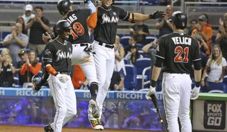 Miami Marlins' Giancarlo Stanton, second from right, celebrates with teammates after he hit a home run scoring Miguel Rojas (19) and Dee Gordon, left, as Christian Yelich (21) watches during the fourth inning of a baseball game against the Colorado Rockies, Saturday, Aug. 12, 2017, in Miami. (AP Photo/Wilfredo Lee)