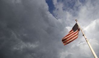An American flag flaps in the wind as storm clouds build over the main post office late Friday, Aug. 11, 2017, in Denver. Forecasters predict that the rainy, cool weather will prevail in the weekend ahead in the region. (AP Photo/David Zalubowski)