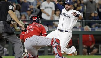 Seattle Mariners' Yonder Alonso, right, slides into a tag at home by Los Angeles Angels catcher Martin Maldonado for the out during the seventh inning of a baseball game Saturday, Aug. 12, 2017, in Seattle. (AP Photo/Elaine Thompson)