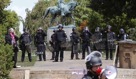 Police in riot gear guard Lee Park after a white nationalist demonstration was declared illegal and the park was cleared in Charlottesville, Va., Saturday, Aug. 12, 2017.  Hundreds of people chanted, threw punches, hurled water bottles and unleashed chemical sprays on each other Saturday after violence erupted at the white nationalist rally. (AP Photo/Steve Helber)