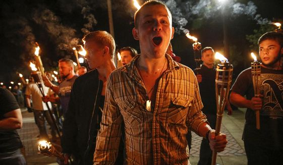 In this photo taken Friday, Aug. 11, 2017, multiple white nationalist groups march with torches through the UVA campus in Charlottesville, Va. Hundreds of people chanted, threw punches, hurled water bottles and unleashed chemical sprays on each other Saturday after violence erupted at a white nationalist rally in Virginia.  (Mykal McEldowney/The Indianapolis Star via AP) ** FILE **