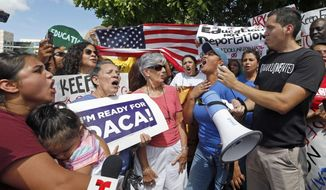 Immigration rights activists chant anti-Trump slogans as they urge Republican lawmakers in Florida to firmly oppose President Donald Trump's proposals to increase funding for immigration enforcement as deadlines for budget decisions near in Congress, Tuesday, Aug. 8, 2017, in Doral, Fla. Dian Alarcon, second from right, said Rep. Mario Diaz-Balart's office told a smaller group on Tuesday the border wall measure would likely not be approved in the Senate. Diaz-Balart's chief of staff Cesar Gonzalez told members of the media he would not comment. (AP Photo/Alan Diaz)