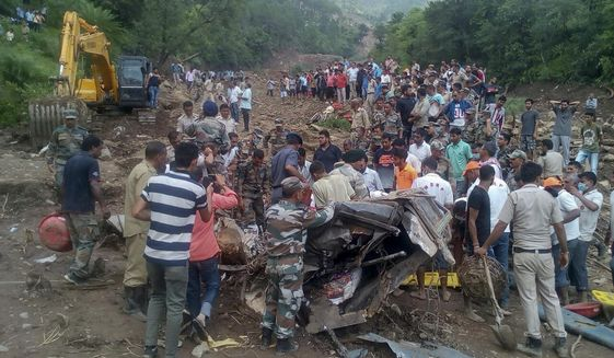 Army soldiers and rescue workers search for bodies of landslide victims even as they try to pull out two buses that were covered in mud after a landslide triggered by heavy monsoon rain in Urla village, Himachal Pradesh state, India, Sunday, Aug. 13, 2017. The landslide that occurred early Sunday buried part of a highway, trapping two buses and at least three cars. (AP Photo/Shailesh Bhatnagar)