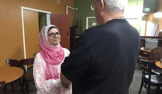 In this July 10, 2017 photo, Moina Shaiq speaks to a man after a Meet a Muslim event at Bronco Billy's Pizza Palace in Fremont, Calif. Shaiq discussed the importance of the hijab, the head scarf, and the niqab, the face covering, as well as the differences between Sunnis and Shias. She also spoke about the rights of women in Islam, and what it's like to be an American-Muslim today in her one-hour talks. (AP Photo/Kristin J. Bender)