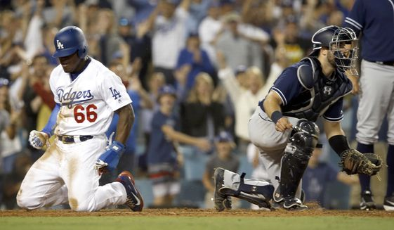 Los Angeles Dodgers' Yasiel Puig, left, reacts after scoring the third run on a single by Corey Seager, as San Diego Padres catcher Austin Hedges, right, turns to look if there is another play, during the sixth inning of a baseball game in Los Angeles, Saturday, Aug. 12, 2017. (AP Photo/Alex Gallardo)