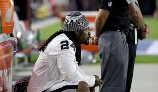 Oakland Raiders running back Marshawn Lynch (24) sits during the national anthem prior to the team's NFL preseason football game against the Arizona Cardinals, Saturday, Aug. 12, 2017, in Glendale, Ariz. (AP Photo/Rick Scuteri)