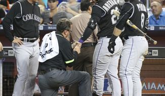 Colorado Rockies' Nolan Arenado, second from left, is checked out by a trainer as manager Bud Black, left, and left fielder Gerardo Parra (8) look on, after being hit by a pitch during the fifth inning of a baseball game against the Miami Marlins, Sunday, Aug. 13, 2017, in Miami.  Arenado left the game after being hit on the left hand by an 88-mph fastball thrown by Vance Worley. The Marlins defeated the Rockies 5-3. (AP Photo/Wilfredo Lee)
