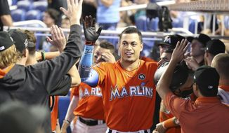 Miami Marlins' Giancarlo Stanton, center, is congratulated by teammates after he hit a home run during the third inning of a baseball game against the Colorado Rockies, Sunday, Aug. 13, 2017, in Miami. (AP Photo/Wilfredo Lee)