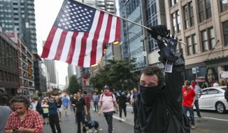 A person burns an American flag Sunday, Aug. 13, 2017, in Seattle. Hundreds of demonstrators and counter-protesters converged in downtown Seattle one day after violent clashes in Charlottesville, Va. (Grant Hindsley/seattlepi.com via AP)