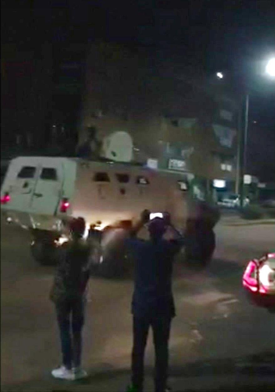 This image taken from video, early Monday, Aug. 14, 2017, shows an armoured vehicle driving down a street after an attack in Ouagadougou, Burkina Faso. Suspected Islamic extremists opened fire at a Turkish restaurant in the capital of Burkina Faso late Sunday, killing at least 18 people in the second such attack on a restaurant popular with foreigners in the last two years. (@Yabsi1er via AP)