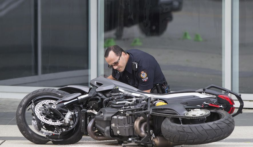 "A police officer examines a motorcycle after a female stunt driver working on the movie ""Deadpool 2"" died after a crash on set, in Vancouver, B.C., on Monday Aug. 14, 2017. Vancouver police say the driver was on a motorcycle when the crash occurred on the movie set on Monday morning. (Darryl Dyck/The Canadian Press via AP)"