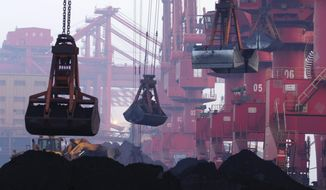 In this June 6, 2015, photo, heavy machines move imported iron ore at the dock in Rizhao in eastern China's Shandong province. (Chinatopix via AP) **FILE**