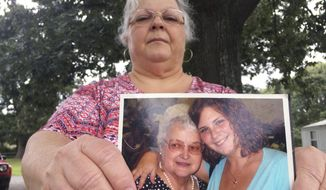 Susan Bro, the mother of Heather Heyer, holds a photo of Bro's mother and her daughter, Monday, Aug. 14, 2017, in Charlottesville, Va. Heyer was killed Saturday, Aug. 12, 2017, when police say a man plowed his car into a group of demonstrators protesting the white nationalist rally. Bro said that she is going to bare her soul to fight for the cause that her daughter died for. (AP Photo/Joshua Replogle)