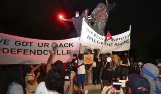 Protesters climb and spray-paint a Confederate monument Sunday, Aug. 13, 2017, at Piedmont Park in Atlanta. The peace monument at the 14th Street entrance depicts an angel of peace stilling the hand of a Confederate soldier about to fire his rifle. Protesters decrying hatred and racism converged around the country on Sunday, saying they felt compelled to counteract the white supremacist rally that spiraled into deadly violence in Virginia. (Curtis Compton/Atlanta Journal-Constitution via AP)