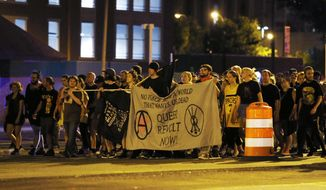Protesters march on Broad Street late Sunday Aug. 13, 2017, in Richmond, Va. The group marched through the Fan District to the Lee Monument to Jackson Ward. The march was held a day after a white supremacist rally spiraled into deadly violence in Charlottesville, Va. (Shelby Lum/Richmond Times-Dispatch via AP)