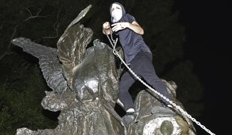 A protester climbs a Confederate monument with a chain in an attempt to topple it Sunday, Aug. 13, 2017, in Atlanta. The peace monument at the 14th Street entrance depicts an angel of peace stilling the hand of a Confederate soldier about to fire his rifle. Protesters decrying hatred and racism converged around the country on Sunday, saying they felt compelled to counteract the white supremacist rally that spiraled into deadly violence in Virginia. (Curtis Compton/Atlanta Journal-Constitution via AP)