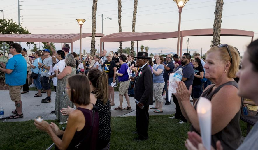 People stand in solidarity with the victims in Charlottesville, Va., during a vigil at the Rev. Dr. Martin Luther King Jr., Memorial Statue in North Las Vegas, Nev., Sunday, Aug. 13, 2017. Protesters decrying hatred and racism converged around the country on Sunday, saying they felt compelled to counteract the white supremacist rally that spiraled into deadly violence in Virginia. (Elizabeth Brumley/Las Vegas Review-Journal via AP)