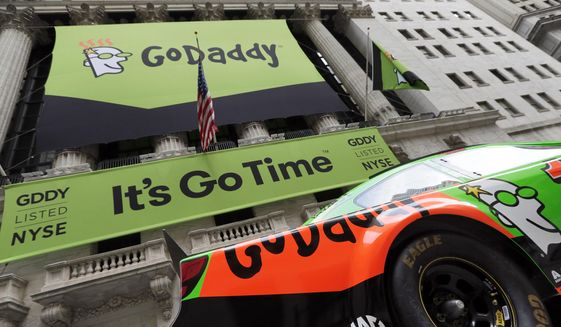 In this April 1, 2015, photo, GoDaddy signage and a race car announce the company's IPO, in front of the New York Stock Exchange in New York. (AP Photo/Richard Drew) **FILE**
