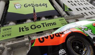 FILE - In this April 1, 2015, file photo, GoDaddy signage and a race car announce the company's IPO, in front of the New York Stock Exchange in New York. GoDaddy announced on Aug. 13, 2017, that has given a prominent white nationalist website that promoted a Virginia rally that ended in deadly violence 24 hours to move its domain to another provider because the site has violated GoDaddy's terms of service.  (AP Photo/Richard Drew, File)