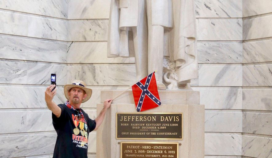 """This photo taken July 24, 2017, shows James Hendrickson, Corbin, Ky., taking a """"selfie"""" with the Jefferson Davis Statue following a rally in support of keeping the statue of Confederate president Jefferson Davis in the Capitol, held on the steps of the State Capitol in Frankfort, Ky. The Kentucky chapter of the Sons of Confederate Veterans organized the rally. After the photo, he attached the flag to the statue. Kentucky's NAACP is renewing efforts to have the statue removed from the Capitol Rotunda in the aftermath of deadly violence in Charlottesville, Va. (Charles Bertram/Lexington Herald-Leader via AP)"""