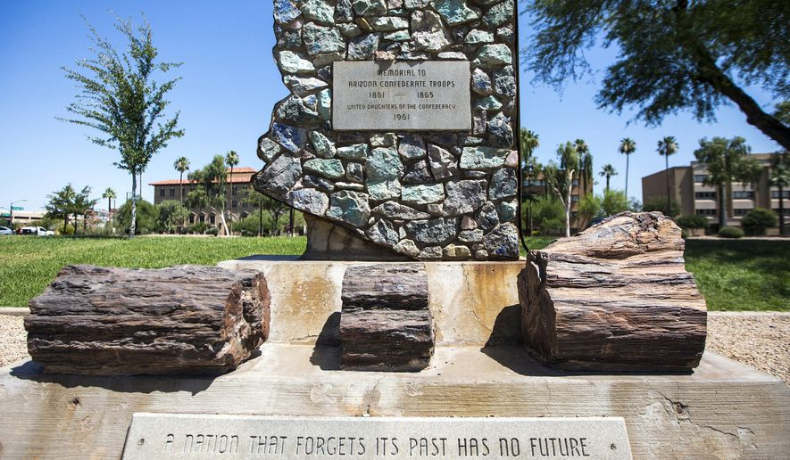 FILE - This June 5, 2017 file photo shows a monument to Arizona Confederate soldiers, presented by the United Daughters of the Confederacy in 1961, amid other memorials at Wesley Bonin Memorial Plaza on the grounds of the Capitol complex in Phoenix. Arizona Gov. Doug Ducey on Monday, Aug. 14, 2017 condemned the white supremacist groups that gathered in Virginia over the weekend to protest the removal of Confederate monuments. But the Republican governor again refused to heed calls from civil rights leaders to take the lead in pushing to remove six Confederate monuments in Arizona. (AP Photo/Angie Wang, File)