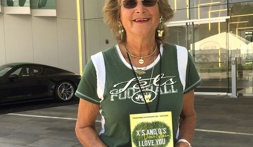"Former New York Jets scout Connie Carberg poses with a recently released book, ""X's And O's Don't Mean I Love You,"" outside the Jets practice facility in Florham Park, N.J., Wednesday, Aug. 9, 2017. How she helped deliver the sack-dancing Mark Gastineau to the Jets is just one of the many fascinating behind-the-scenes tales told by Carberg and author Elisabeth Meinecke. Gastineau went on to become one of the Jets' best and most popular players _ and helped cement Carberg's place in NFL history as the league's first female scout. (AP Photo/Dennis Waszak Jr.)"