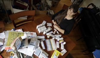 In this Aug. 10, 2017, photo, Sara Hayden poses for a photo with some of her medications at home in Half Moon Bay, Calif. Hayden lost her job as a data researcher because of medical problems and is now covered by Medi-Cal, as Medicaid is called in California. She has rheumatoid arthritis, and the medication she has to take to keep the disease in check cost thousands of dollars a month. The Medicaid program is a 1960s Great Society creation long criticized by conservatives. But it seems to have emerged even stronger after the Republican failure to pass health overhaul legislation. (AP Photo/Marcio Jose Sanchez)