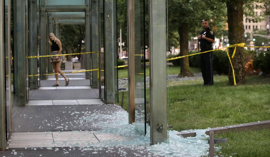 A passerby, left, and a law enforcement official, right, stand near broken glass at the New England Holocaust Memorial on Monday, Aug. 14, 2017, in Boston. Police say a person is in custody for allegedly vandalizing the memorial. It's the second time the memorial has been damaged this summer. Police say the suspect smashed a glass panel Monday. (AP Photo/Steven Senne)