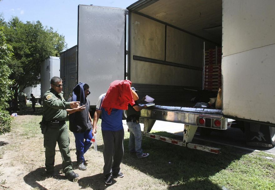 In this Sunday Aug. 13, 2017, file photo, Border Patrol officers escort a group of immigrants to a van after a group was found in the tractor-trailer in Edinburg, Texas. Police in Texas acting on a tip found the immigrants locked inside the tractor-trailer parked at a gas station about 20 miles (30 kilometers) from the border with Mexico, less than a month after 10 people died in the back of a hot truck with little ventilation in San Antonio. (Delcia Lopez/The Monitor via AP)