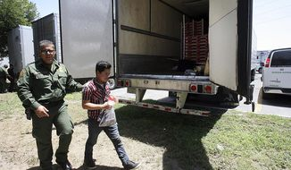 In this Sunday, Aug. 13, 2017, photo, Border Patrol officers escort a group of immigrants to a van in Edinburg, Texas. Police in Texas acting on a tip found the immigrants locked inside the tractor-trailer parked at a gas station about 20 miles (30 kilometers) from the border with Mexico, less than a month after 10 people died in the back of a hot truck with little ventilation in San Antonio. (Delcia Lopez/The Monitor via AP) ** FILE **