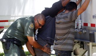 In this Sunday, Aug. 13, 2017, photo, a Border Patrol officer pats down several of the men that were found with a group of immigrants in a tractor-trailer in Edinburg, Texas. Police in Texas acting on a tip found the immigrants locked inside a tractor-trailer parked at a gas station about 20 miles (30 kilometers) from the border with Mexico, less than a month after 10 people died in the back of a hot truck with little ventilation in San Antonio. (Delcia Lopez/The Monitor via AP)