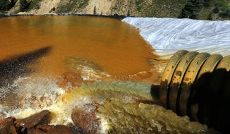 In this Aug. 14, 2015, file photo, water flows through a series of sediment retention ponds built to reduce heavy metal and chemical contaminants from the Gold King Mine wastewater accident in the spillway about a quarter mile downstream from the mine outside Silverton, Colo. Environmental Protection Agency Administrator Scott Pruitt said Aug. 4, 2017 that he will consider paying for economic damages from the spill, something the EPA previously said it could not do because of laws protecting the government from lawsuits. His comments came during a tour of the mine on the eve of the second anniversary of the spill. (AP Photo/Brennan Linsley, File)