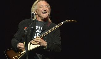 "FILE - In this Jan. 15, 2014, file photo, Joe Walsh of The Eagles performs on the ""History of the Eagles"" tour at the Forum in Inglewood, California. Walsh and the rest of the Eagles announced Aug. 14, 2017, that they would be heading out on tour with the son of founding member Glenn Frey stepping in for his late father. (Photo by John Shearer/Invision/AP, File)"