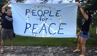 "Guam residents hold ""people for peace"" as about a hundred people gathered at Chief Kepuha Park in Hagatna, Guam for a rally for peace Monday, Aug. 14, 2017. The U.S. territory has been the subject of threats from North Korea in its escalating war of words with the U.S. President Donald Trump's administration. (AP Photo/Tassanee Vejpongsa)"