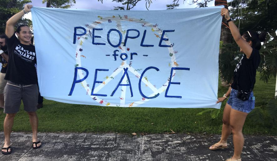 """Guam residents hold """"people for peace"""" as about a hundred people gathered at Chief Kepuha Park in Hagatna, Guam for a rally for peace Monday, Aug. 14, 2017. The U.S. territory has been the subject of threats from North Korea in its escalating war of words with the U.S. President Donald Trump's administration. (AP Photo/Tassanee Vejpongsa)"""