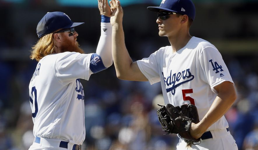 Los Angeles Dodgers third baseman Justin Turner, left, celebrates with shortstop Corey Seager after the Dodgers defeated the San Diego Padres 6-4 in a baseball game in Los Angeles, Sunday, Aug. 13, 2017. (AP Photo/Alex Gallardo)