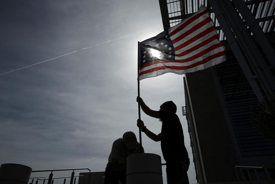 FILE - In this April 24, 2017, file photo, supporters raise a flag outside of the federal courthouse in Las Vegas. A retrial is nearing an end in Nevada for four men facing decades in prison for bringing assault-style weapons to a confrontation that stopped government agents from rounding up cattle near anti-government figure Cliven Bundy's ranch in April 2014. (AP Photo/John Locher, File)