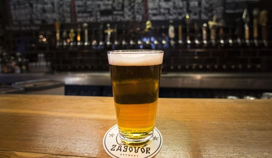 In this July 21, 2017 photo, a glass of craft beer sits on the bar at the Rule Taproom pub in Moscow, Russia. Pint by frothy pint, a hoppy revolution is brewing in Russia. A new generation of craft beer brewers began sprouting in the vodka capital of the world as foreign beers got too expensive and beer-drinkers started looking for alternatives to mass-produced lagers.  (AP Photo/Alexander Zemlianichenko)