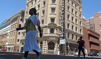 Pedestrians cross a street near the Bank of Stockton in Stockton, Calif. U.S. cities and counties are poring over immigration rules to avoid losing millions in public safety dollars that the Trump administration has threatened to withhold amid a high-stakes clash over sanctuary policies. At least six locations are suing, with Chicago becoming the first so-called sanctuary city to scrutinize a specific grant. (AP Photo/Gosia Wozniacka, File)