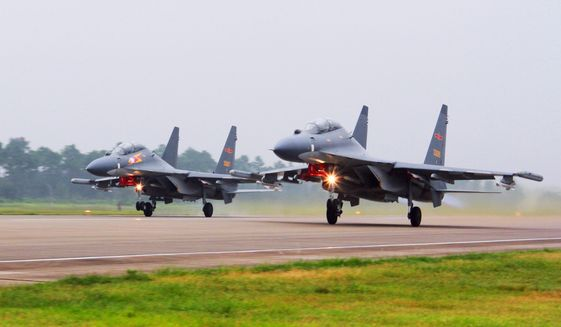 In this undated file photo by China's Xinhua News Agency, two Chinese SU-30 fighter jets take off from an unspecified location to fly a patrol over the South China Sea. (Jin Danhua/Xinhua via AP, File)