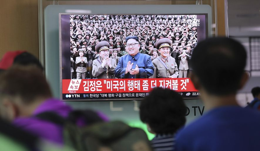 "People watch a TV screen showing a local news program reporting about North Korean military's plans to launch missiles into waters near Guam, with an image of North Korean leader Kim Jong Un, at Seoul Train Station in Seoul, South Korea, Tuesday, Aug. 15, 2017. North Korea said Tuesday that leader Kim Jong Un was briefed on his military's plans to launch missiles into waters near Guam as part of an effort to create ""enveloping fire"" near the U.S. military hub in the Pacific. The letters read ""Kim Jong Un, would watch a little more U.S.'s behavior."" (AP Photo/Lee Jin-man)"