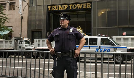 Police stands guard and trucks are parked in front of Trump Tower as a security measure against protestors ahead President Donald Trump's first visit to the building since taking office, New York, Monday, Aug. 14, 2017. (AP Photo/Andres Kudacki)